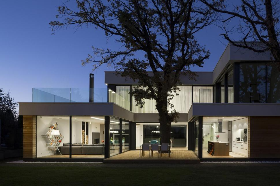 Home incorporates thermal balance of 2 oak trees in design for Case con vetrate