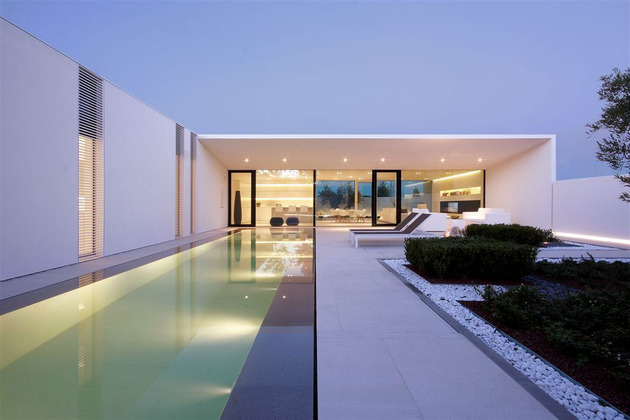 serene-white-house-with-walled-outdoor-space-7-evening-pool-far.jpg