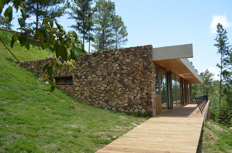 Built Into Slope Uses Hillside For Cooling