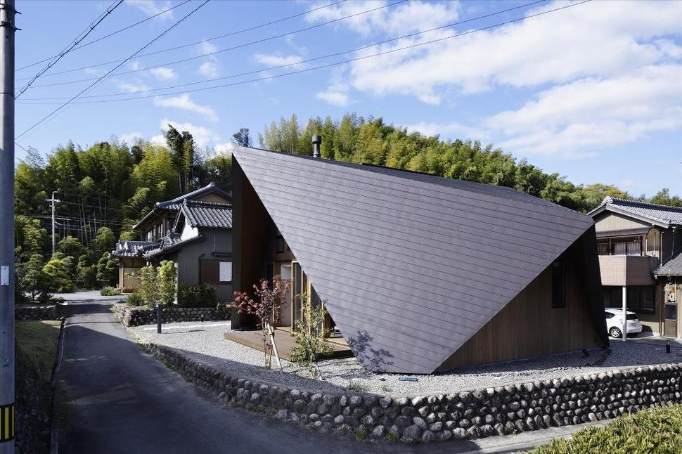Home surrounded by rock wall and protected by folded roof for Home architecture analogy