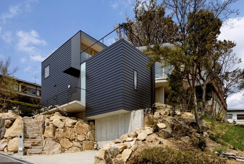 Steep slope house with bookshelf lined interior for House foundation on slope