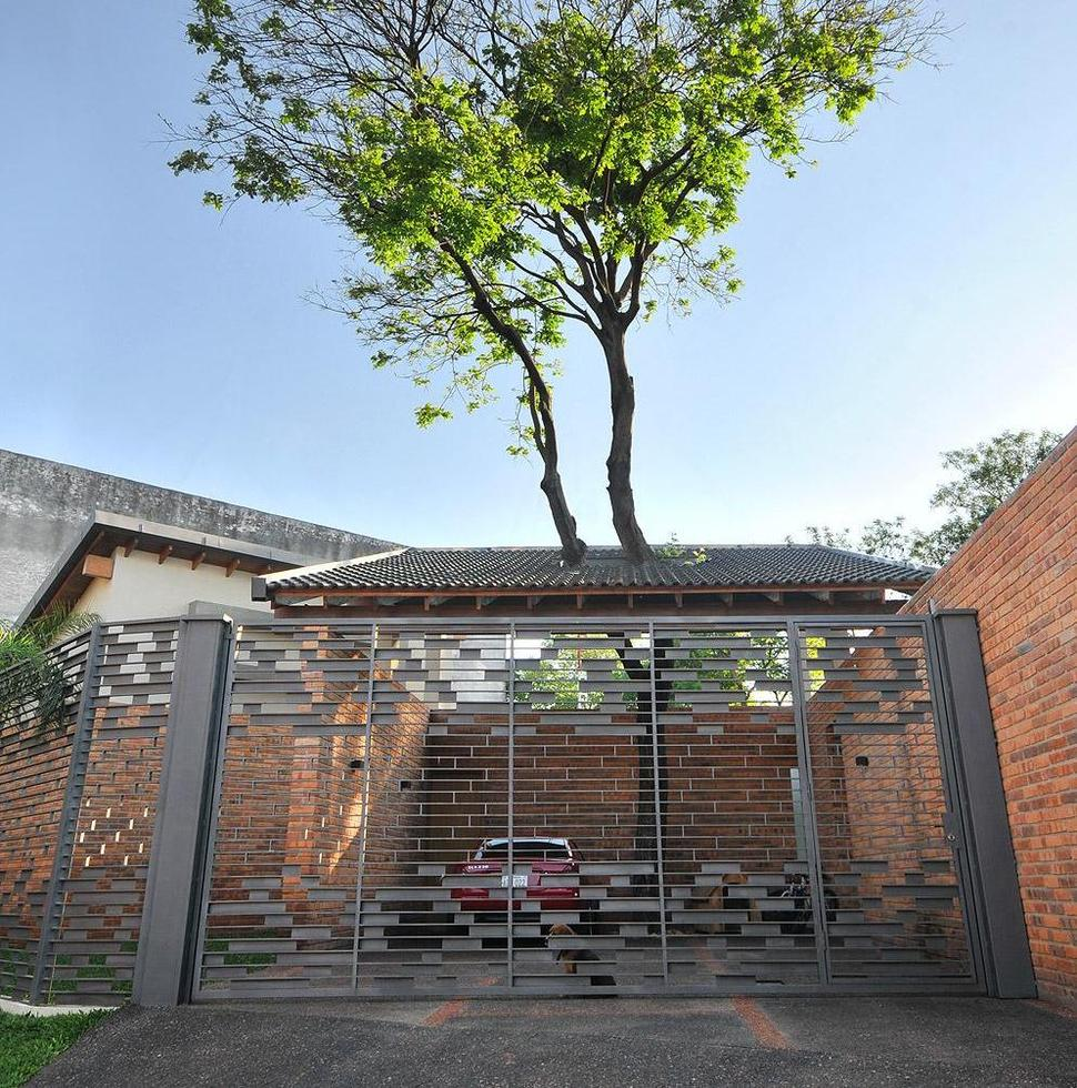 Tree pierces roof and other daring details within brick home for Brick carport