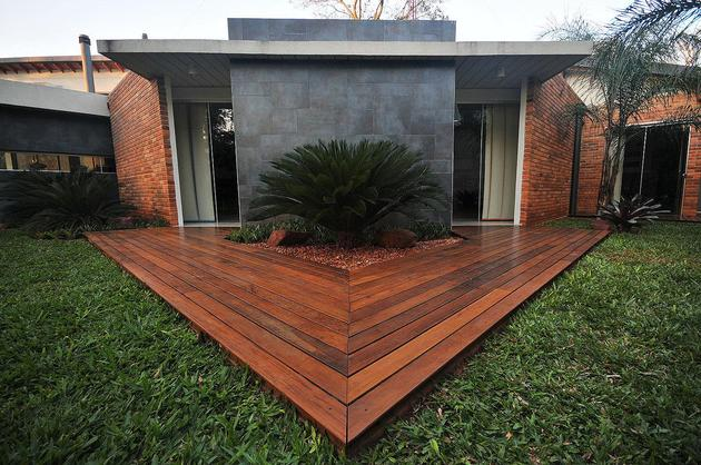 Tree pierces roof and other daring details within brick home for Pentagon shaped house plans
