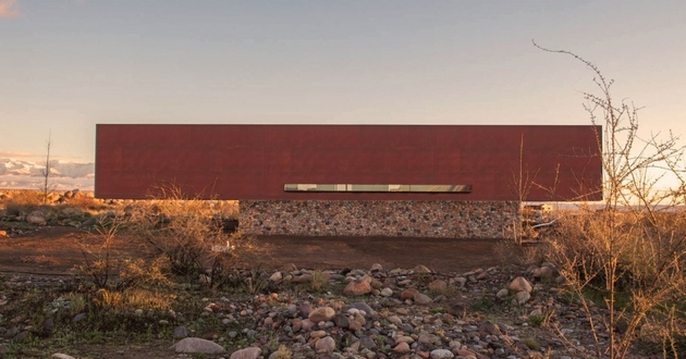 1 minimalist house river rock rusty steel thumb 630xauto 63591 Beautiful Simple Home Uses 5 Building Materials: Stone, Steel, Wood, Concrete, Glass