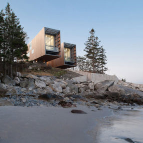 Boat inspired wood house hanging over the ocean