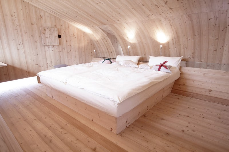 compact irregularly shaped austrian mountain house on stilts 18 master bed