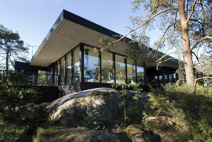 Modern wooden vacation house built on rocks for Modern wood house