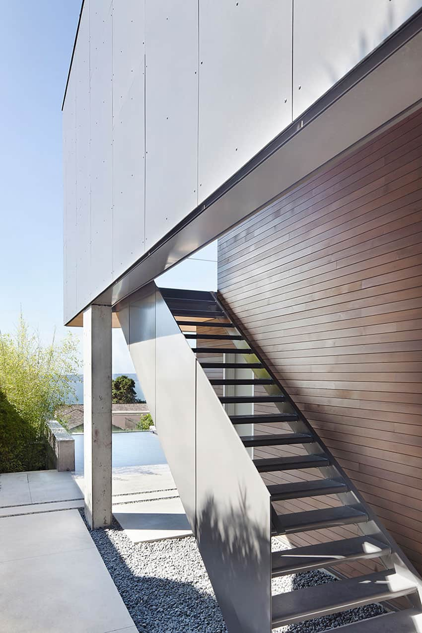 Sleek slope house with interior featuring concrete for Exterior stairs designs of indian houses