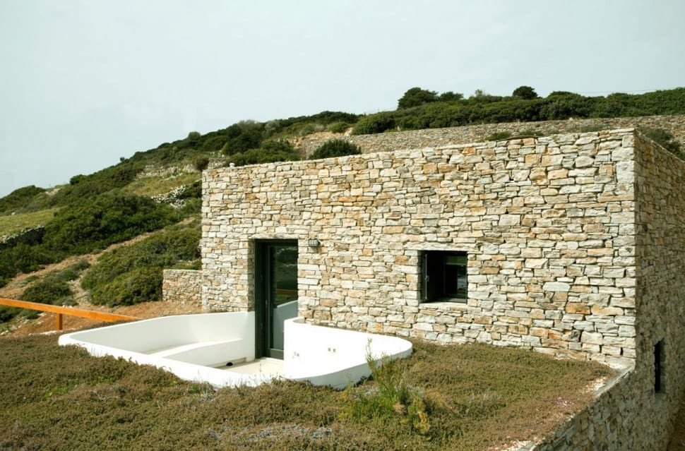 Stepped house with stone walls and standout white cube for Build a stone house