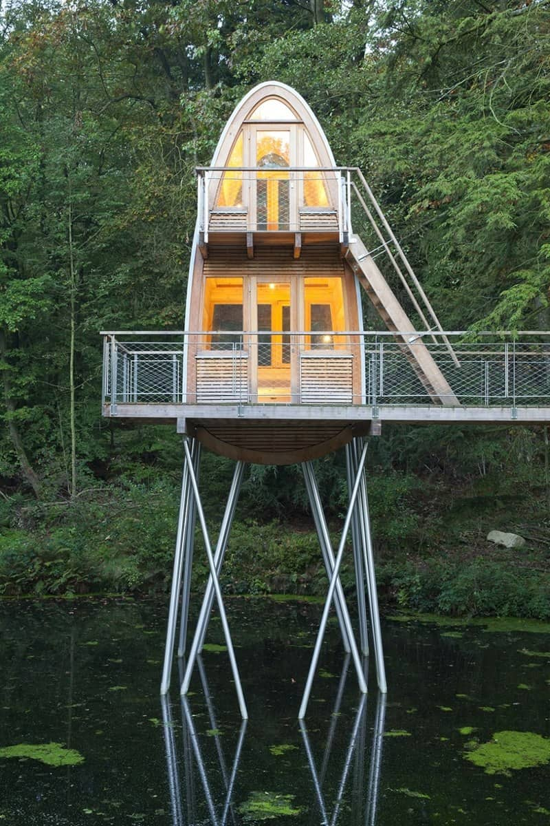 View in gallery unusual-forest-cabin-on-stilts-over-pond-4-