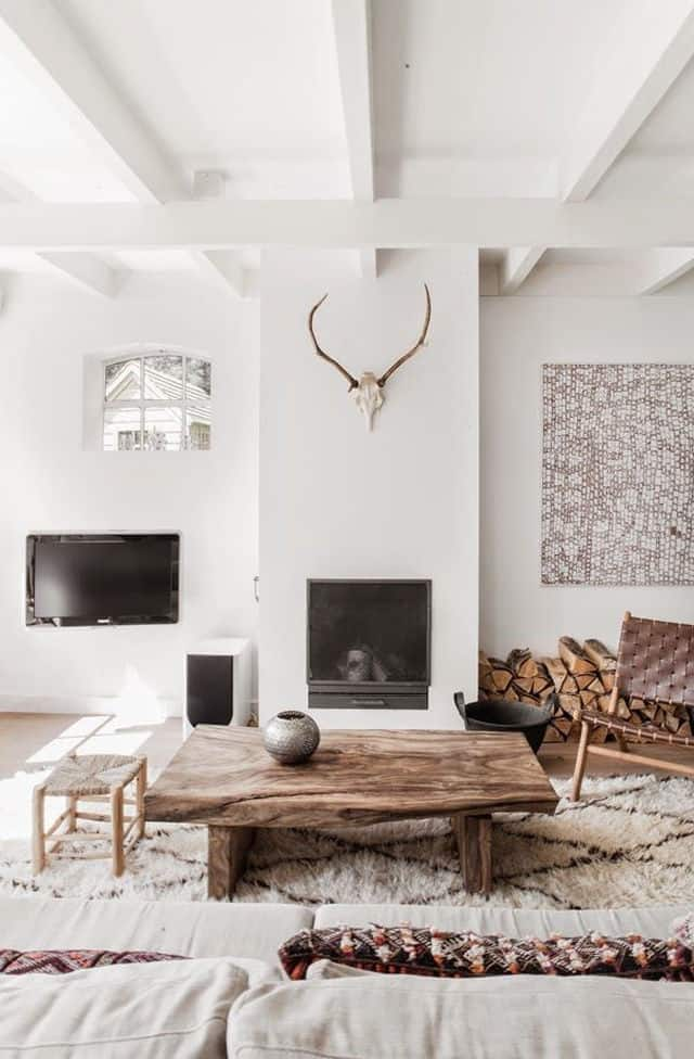 In this living room above the all white design is warmed up by natural wood via the flooring and the country style furnishings and tying the two
