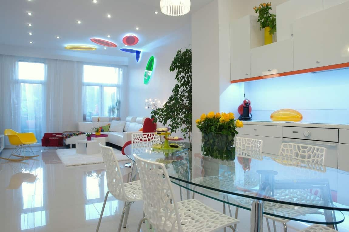 The dashes of color in this all white apartment are made even more vibrant with the use of led lights in fact the colorful discs on the living room ceiling